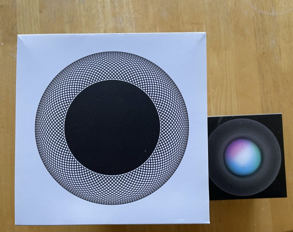Original HomePod box next to the HomePod mini box, top view.